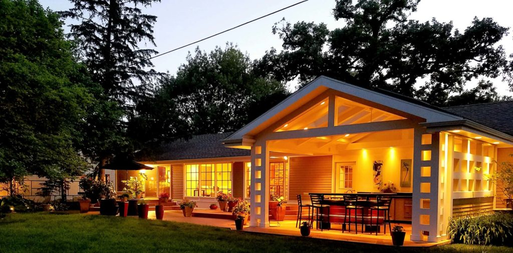 Backyard view of a well lit patio, including an open walled room