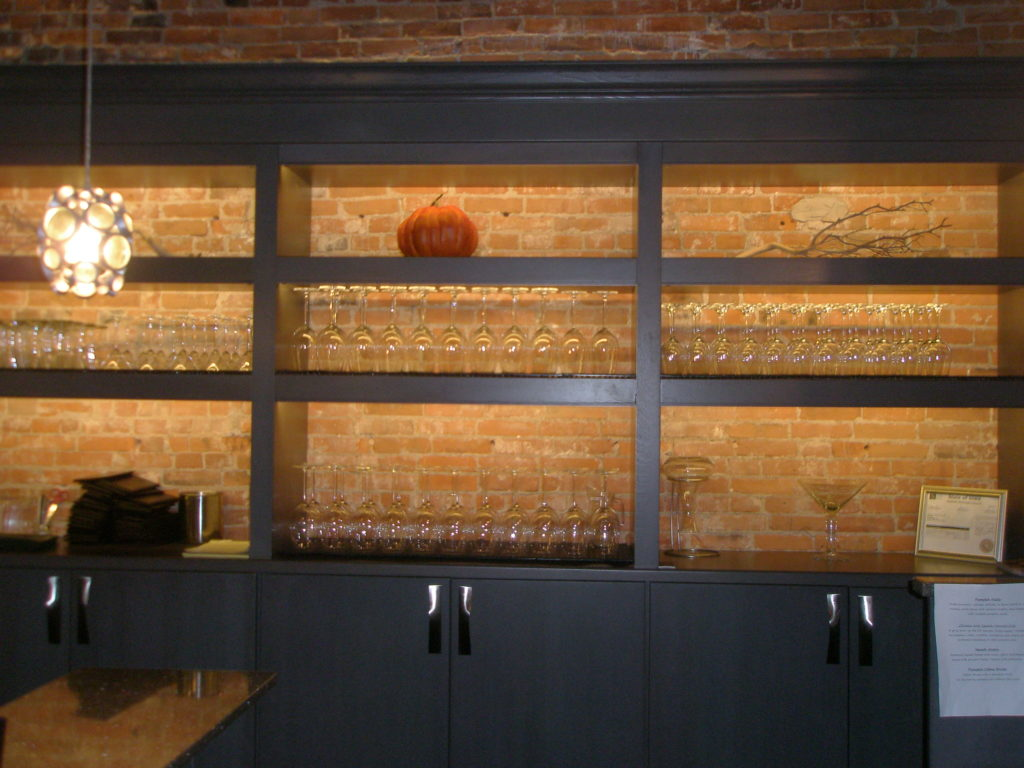Custom lighting on shelving units at the Olympus Bar